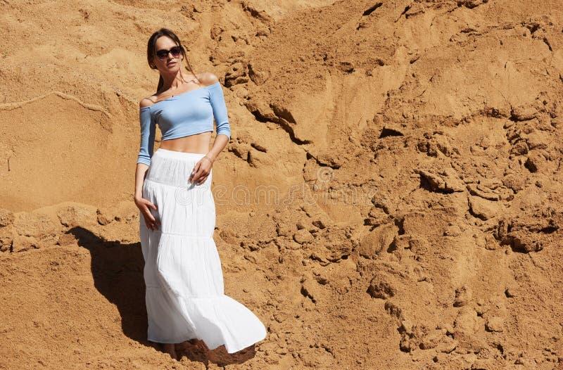 Modna kobieta stoi na gorÄ…cym piasku zdjęcie royalty free