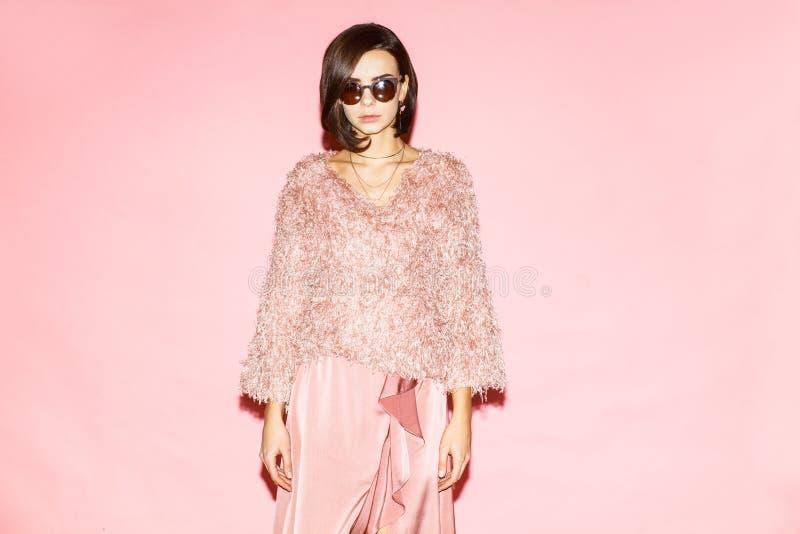 Modna kobieta w menchiach ubiera na różowym tle zdjęcia royalty free