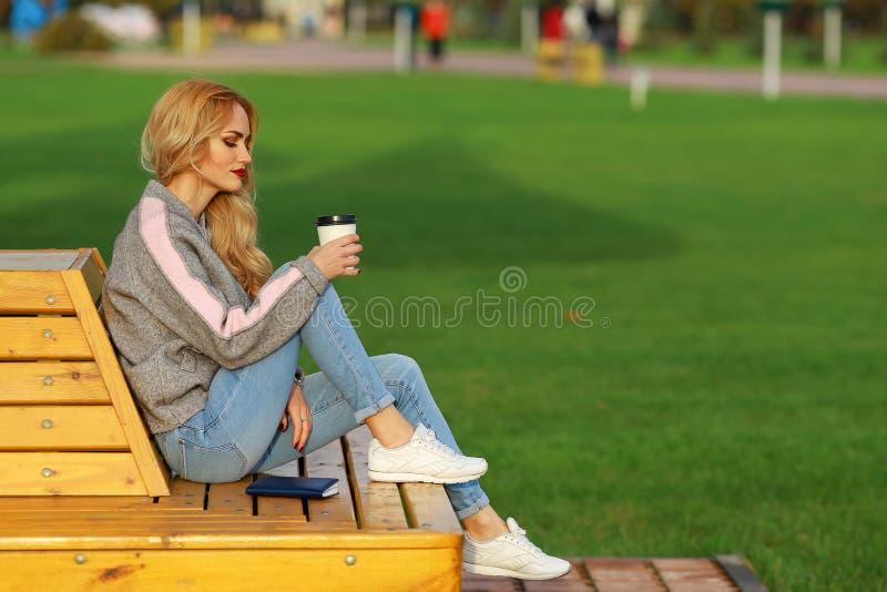 Modna kobieta w obsiadaniu na ławce w miasto parku Pijący takeaway kawę, writing i rysunek coś w notatniku zdjęcie royalty free