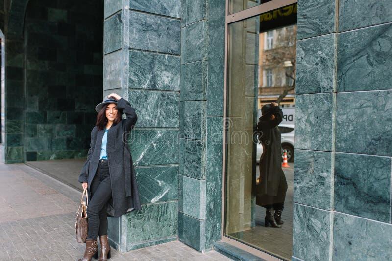 Modna młoda kobieta w popielatym żakiecie, kapeluszowy odprowadzenie na ulicie w centrum miasta Ono uśmiecha się kamera, prawdziw obrazy royalty free