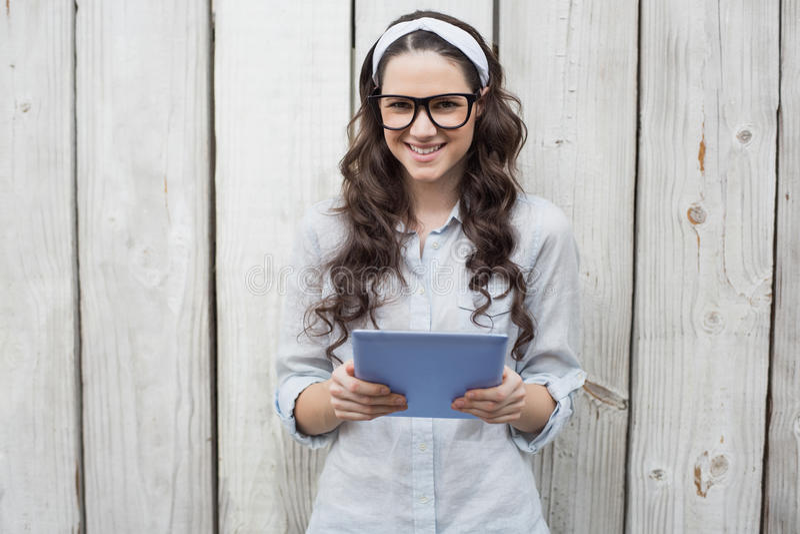 Modna młoda kobieta z eleganckimi szkłami używać pastylka komputer osobistego obrazy royalty free