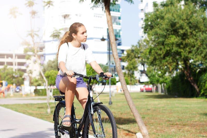 Modna młoda nastoletnia dziewczyna w skrótach i koszulce jedzie bicykl w lato parku obrazy stock