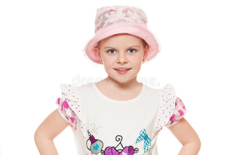 Modna mała śliczna dziewczyna w koszula i kapeluszu odizolowywających na białym tle, fotografia royalty free
