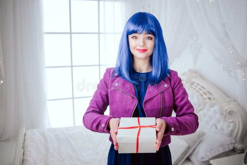 Modna pokraka Portret splendor uśmiechnięta piękna kobieta z błękitnym włosy trzyma prezent w białej sypialni zdjęcia stock