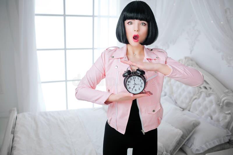 Modna pokraka Splendor emocjonalna piękna kobieta z krótkim czarni włosy trzyma zegar podczas gdy stojący w bielu obrazy stock