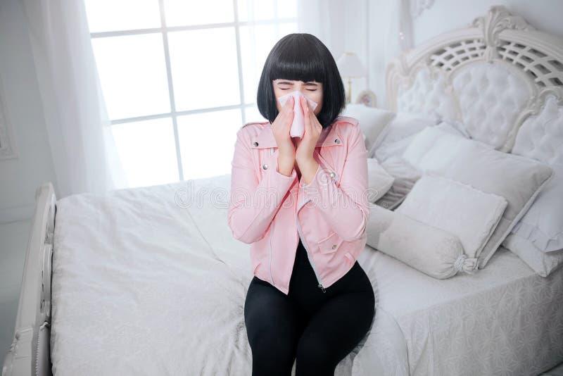 Modna pokraka Splendor kobieta z krótkim czarni włosy jest podmuchowym nosem i cierpieniem od bolączki w białej sypialni zdjęcia stock