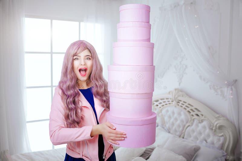 Modna pokraka Splendor szczęśliwa piękna kobieta z długim lilym włosy trzyma różowych pudełka podczas gdy stojący w bielu zdjęcia royalty free