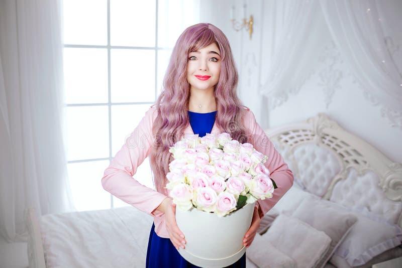 Modna pokraka Splendor uśmiechnięta piękna kobieta stojąca z długim lilym włosy trzyma białego pudełko z kwiatami podczas gdy obraz royalty free