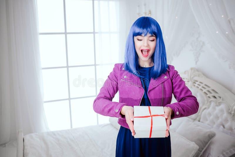 Modna pokraka Splendor zaskakująca piękna kobieta z błękitnym włosy trzyma prezent w białej sypialni Moda i fotografia stock
