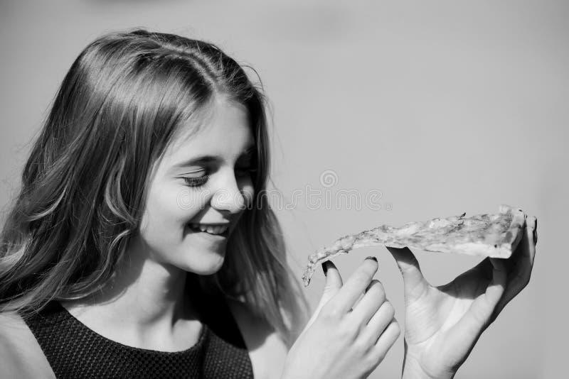 modna target40_0_ kobieta Szczęśliwa ładna dziewczyna ono uśmiecha się z kawałkiem smakowita pizza zdjęcie royalty free