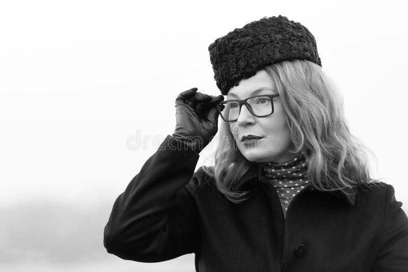 Modna w średnim wieku kobieta patrzeje przez widowisk fotografia stock