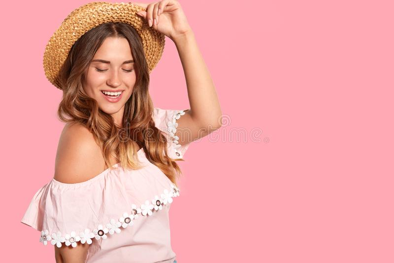 Modna zadowolona Europejska kobiet utrzymań ręka na słomianym kapeluszu, skupiający się puszek, delikatnego uśmiech, stoi z ukosa obrazy royalty free