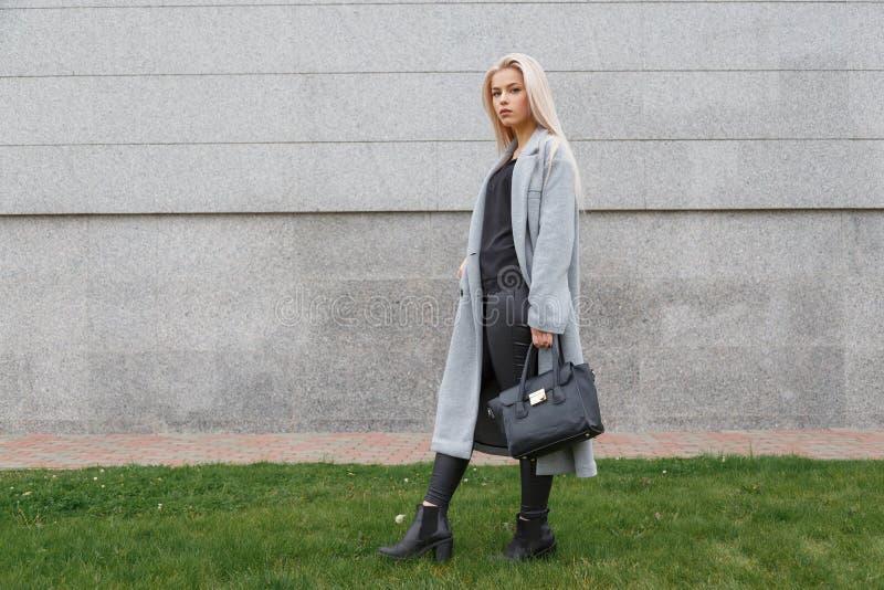 Modnej kobiety pozować plenerowy, trzymający czarną rzemienną torbę, jest ubranym eleganckich buty, elegancki żakiet Żeński mody  zdjęcia stock