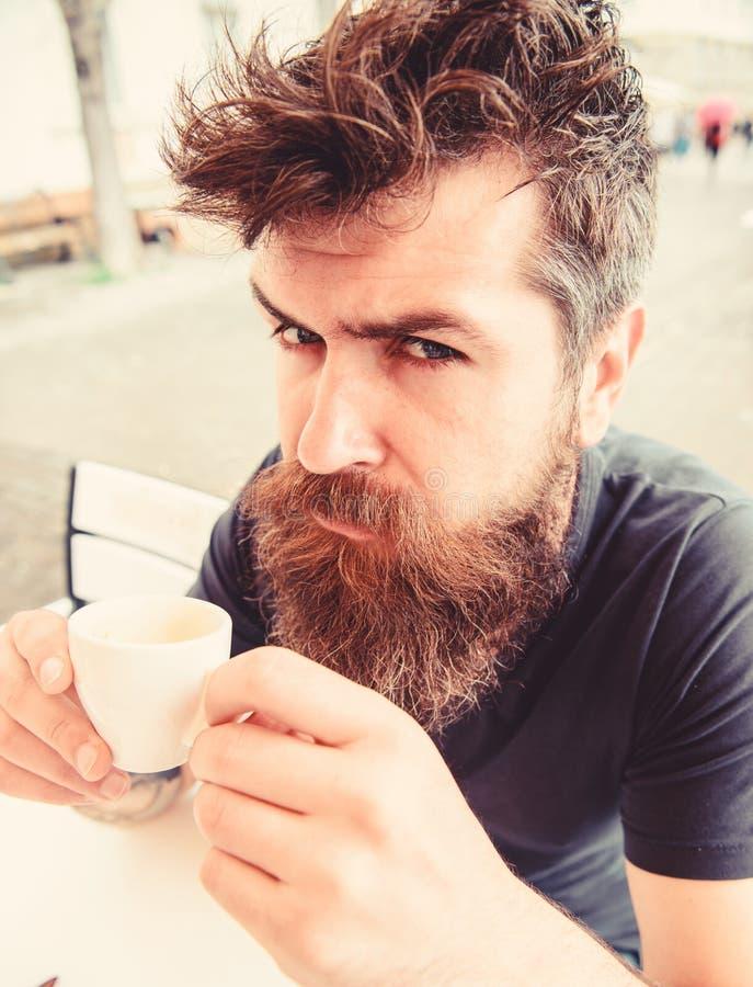 Modniś pije kawowy plenerowego na poważnej surowej twarzy pojęcia stary kawa się wziąć Mężczyzna z brodą i wąsy trzyma filiżankę obraz royalty free