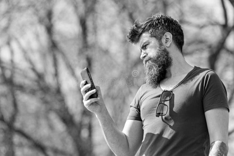 Modniś z brodą używać telefon komórkowego plenerowego Mężczyzna dzwoni z brodą i wąsy na surowej twarzy, natury tło zdjęcia stock