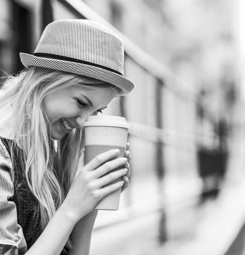 Modniś dziewczyna z filiżanką gorący napój na miasto ulicie obraz stock