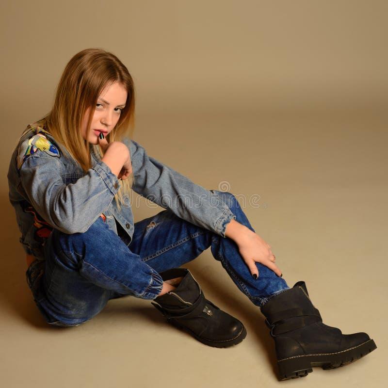 Modniś dziewczyny obsiadanie na podłoga przeciw graybackground zdjęcie royalty free