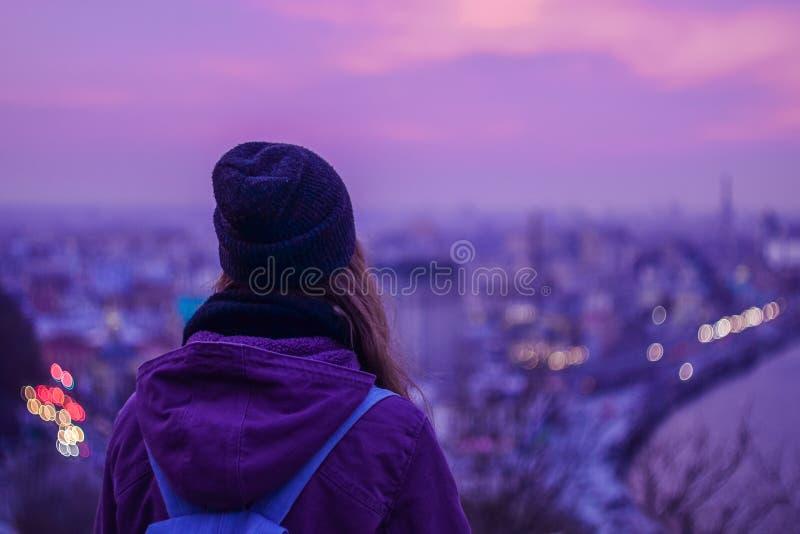Modniś dziewczyny podróżnik patrzeje zima wieczór pejzaż miejskiego, purpurowego fiołkowego niebo i miast światła, zdjęcie royalty free