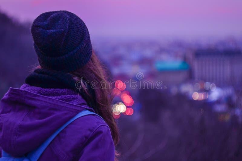 Modniś dziewczyny podróżnik patrzeje zima wieczór pejzaż miejskiego, purpurowego niebo i zamazanych miast światła, zdjęcie stock