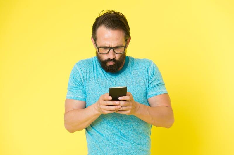 Modniś intrygujący używa smartphone Mężczyzny niewytrawny użytkownik nowożytny smartphone Pobyt w kontakcie z smartphone Łączy on fotografia royalty free