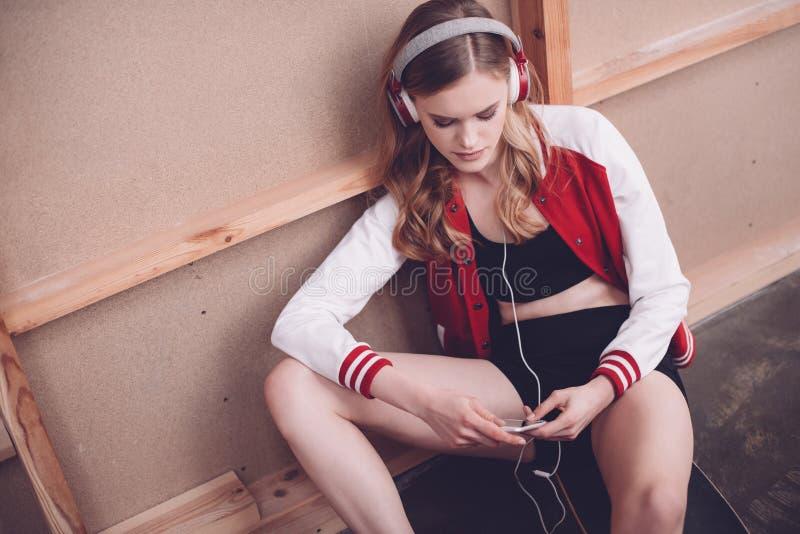 Modniś kobieta siedzi na podłoga z smartphone i hełmofonami obrazy royalty free