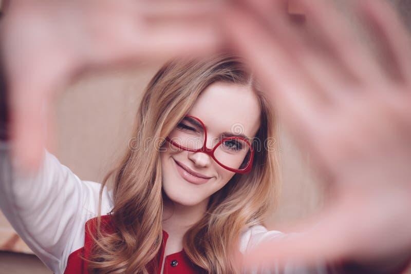 Modniś kobieta z czerwonymi eyeglasses robi otoczce i mruganiu gestykulować ostrość obrazy stock