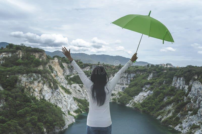 Modniś młoda dziewczyna z zielonym umbella cieszy się zmierzch na szczycie mo obraz stock