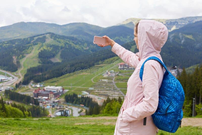Modniś młoda kobieta jest ubranym kapiszon pozycję przy góra wierzchołkiem z jaskrawą menchii kurtką i plecakiem, brać fotografię obraz stock