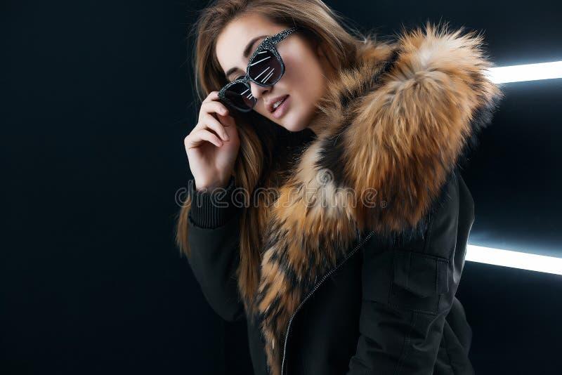 Modniś nastoletnia dziewczyna w okularach przeciwsłonecznych pozuje nad ścianą obrazy stock
