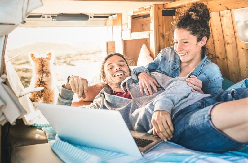 Modniś para podróżuje z psim i używa komputerowym laptopem zdjęcie royalty free