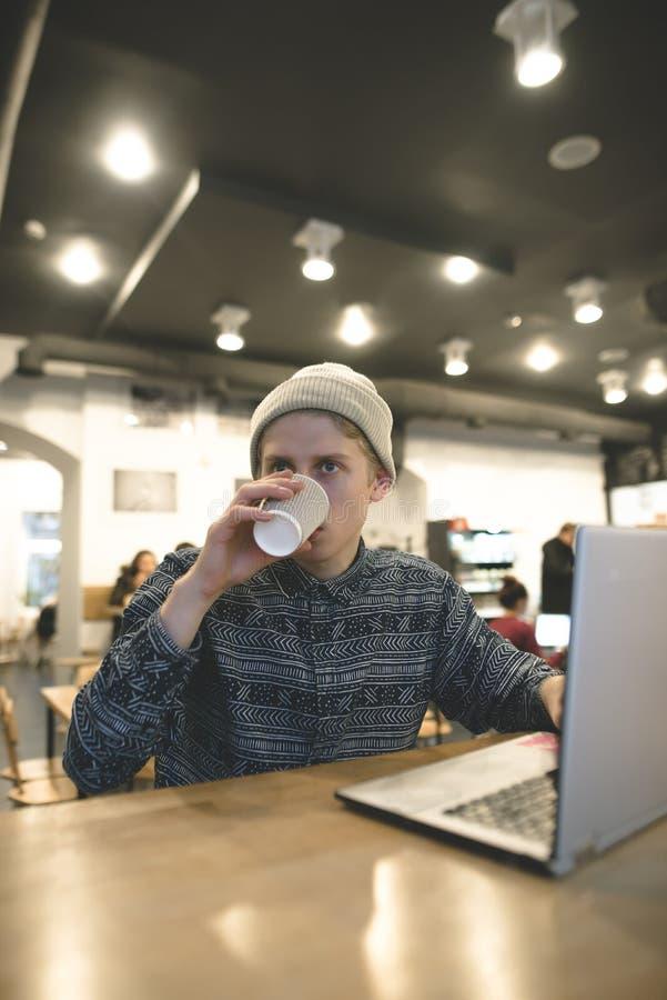 Modniś pije kawę podczas gdy pracujący przy komputerem w wygodnej kawiarni Freelancer pracy dla kawy fotografia royalty free