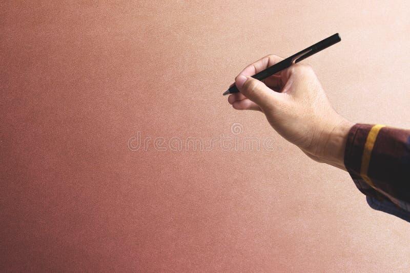 Modniś ręki mienia pióro nad starym rocznik ściany tłem fotografia royalty free