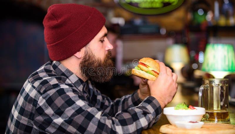 Modniś relaksuje przy pubem Pub jest relaksującym miejscem mieć napój i relaksować Mężczyzna z broda napoju piwem je hamburgeru m fotografia stock