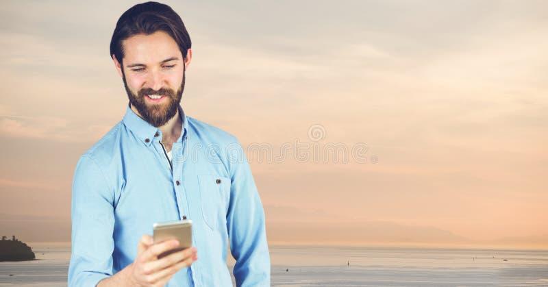 Modniś używa telefon komórkowego przy plażą przeciw niebu obrazy royalty free