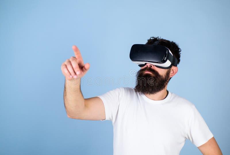 Modniś w VR szkłach sprawdza nowego przyrząd, nowożytny technologii pojęcie Brodaty mężczyzna absorbujący w rzeczywistości wirtua fotografia stock