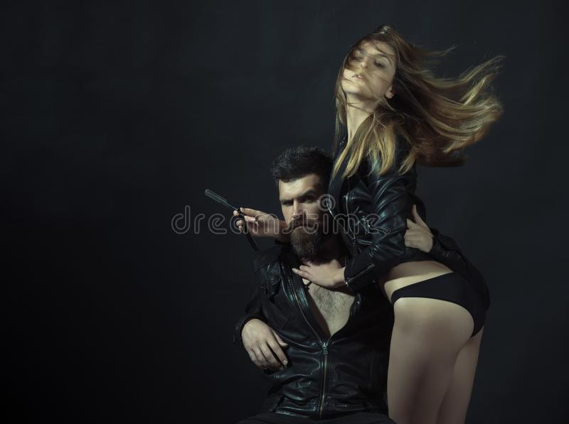 Modniś z brodą i seksowną dziewczyną trzyma prostą żyletkę Fryzjer męski z prostej żyletki pracami na ostrzyżeniu Para seksowna d zdjęcie stock