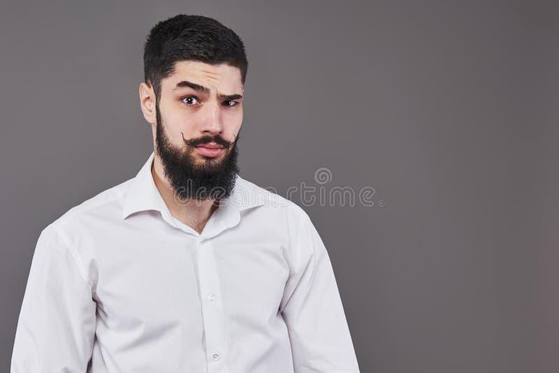 Modniś z poważną twarzą czuć i emocje Facet lub brodaty mężczyzna na popielatym tle Fryzjera męskiego piękno i moda człowieku zdjęcia royalty free