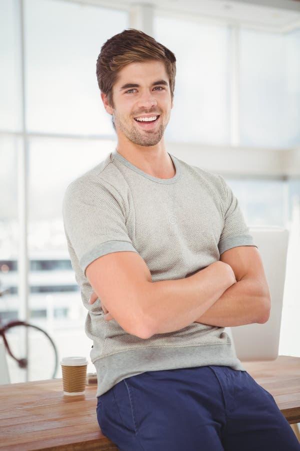 Modniś z rękami krzyżował uśmiecha się podczas gdy siedzący przy biurkiem obrazy stock