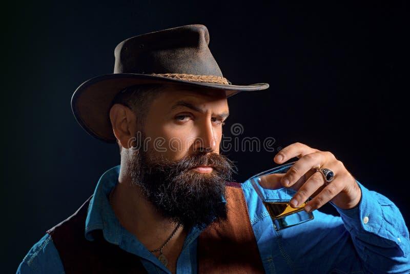 Modni? z brod? i w?sy w kostiumu pije alkohol po dnia roboczego Rozochocony brodaty mężczyzna jest pić drogi obraz royalty free