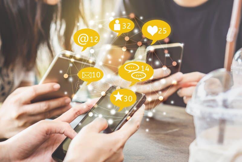 Modnisiów przyjaciele używa mądrze telefonu udzielenie z ogólnospołecznymi środkami obraz royalty free