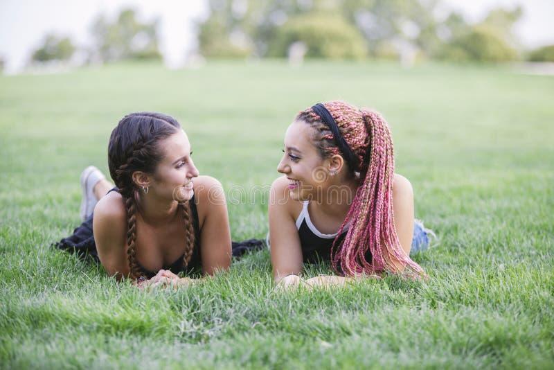 modnisiów nastolatkowie ono uśmiecha się each inny na parku zdjęcie royalty free