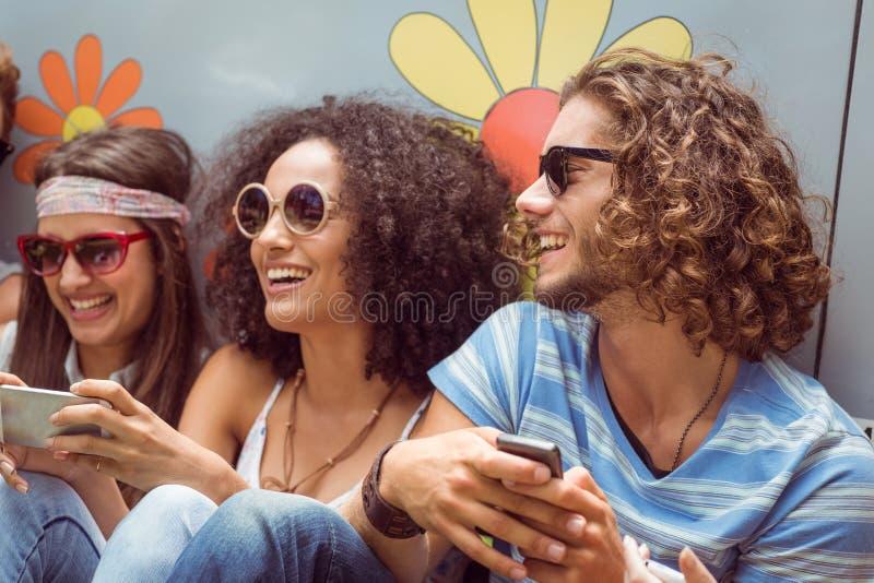 Modnisiów przyjaciele używa ich telefony zdjęcia royalty free