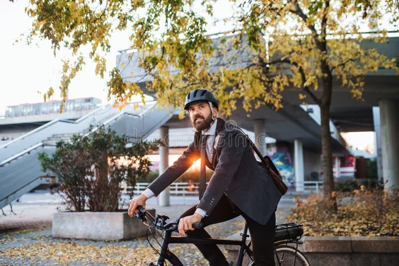 Modnisia biznesmena dojeżdżający z elektrycznym rowerowym podróżować domem od pracy w mieście obrazy stock