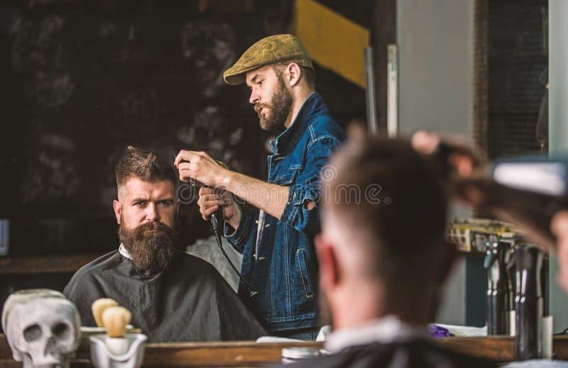 Modnisia brodaty klient dostaje fryzur? Fryzjer m?ski z hairdryer pracuje na fryzurze dla brodatego m??czyzna, zak?ad fryzjerski zdjęcie royalty free