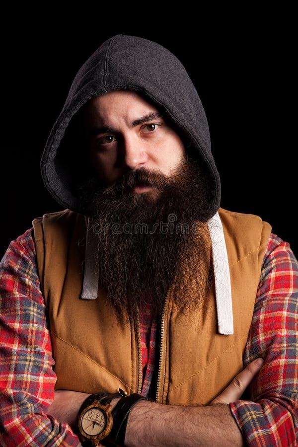Modnisia brodaty mężczyzna jest ubranym kapiszon zdjęcie royalty free