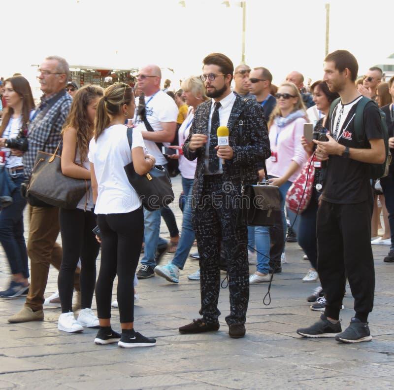 Modnisia dziennikarz przeprowadza wywiad turystów w centrum miasta obrazy stock