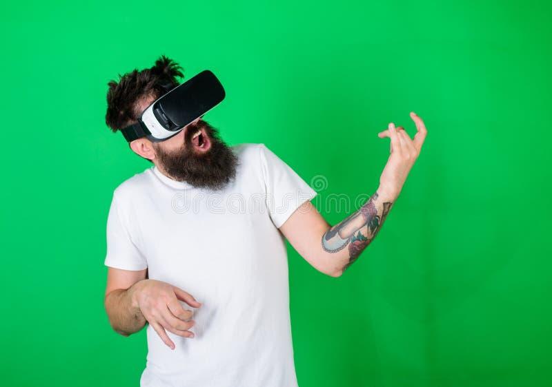 Modnisia gitarzysta na entuzjastycznego twarzy use nowożytnej technologii dla rozrywki Facet z VR szkłami uczy się bawić się muzy obrazy stock