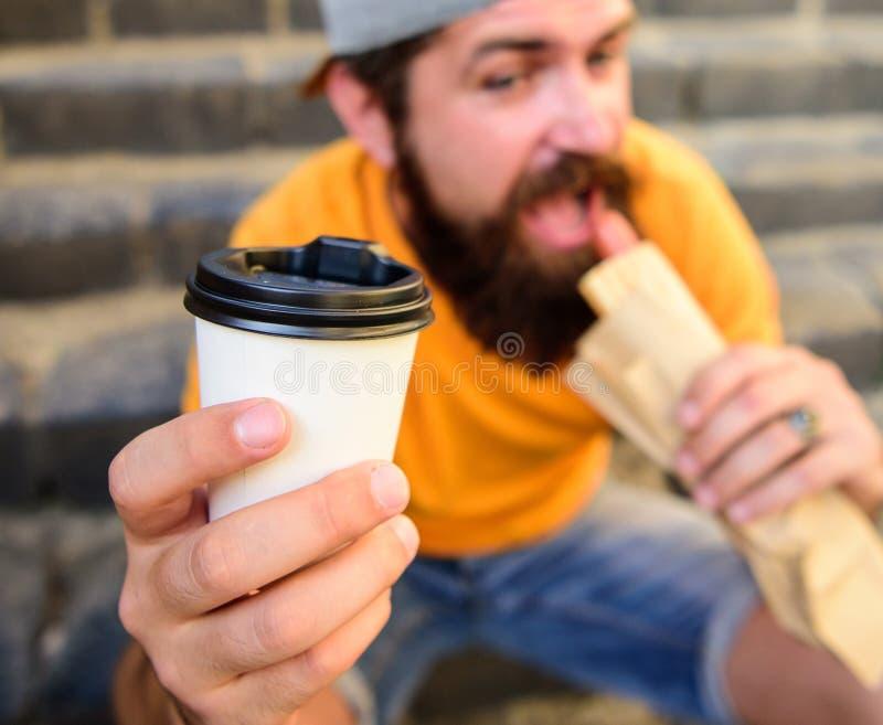 Modnisia kąsek je hot dog Fasta food posiłek dla lunchu Modnisia kąska hot dog chwyta napoju papierowa filiżanka Mężczyzna brodat fotografia royalty free