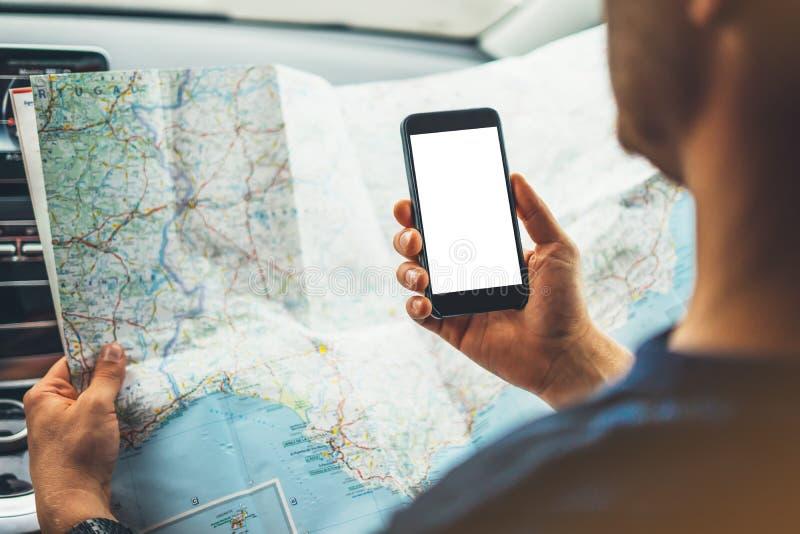 Modnisia mężczyzna patrzeje na nawigaci mapie w samochodzie, turystycznym podróżnika jeżdżeniu i mieniu w samiec ręk smartphone g zdjęcie royalty free