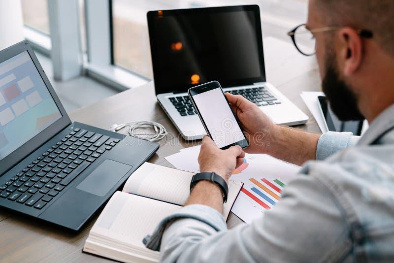 Modnisia mężczyzna siedzi w kawiarni, używa smartphone, pracuje na dwa laptopach Biznesmen czyta ewidencyjną wiadomość w telefoni obraz royalty free
